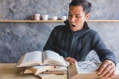 Ein schockierendes Gesicht des Mannes mit vielen Buch muss er gelesen werden lizenzfreie stockbilder