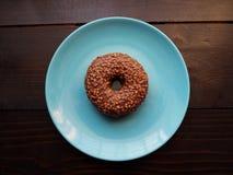 Ein Schokoladendonut auf der blauen Platte stockfotografie