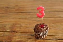 Ein Schokoladenkleiner kuchen mit einer Geburtstagskerze Lizenzfreies Stockbild