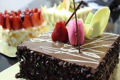 Schokoladenkuchen überstieg mit einer Erdbeere und einem macaron Stockbild