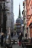 Ein schräg gelegenes gestaltetes Haus des Bauholzes nahe bei einer gotischen Kirche lizenzfreie stockfotos