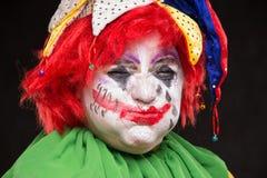 Ein schrecklicher Clown mit einem schrecklichen Make-up und einem Hut lachend auf einem b lizenzfreie stockbilder