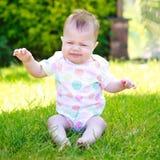 Ein schreiendes und schlängelndes Baby in einer Weste, die auf dem Gras sitzt Lizenzfreie Stockbilder