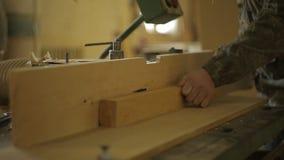 Ein Schreiner an den Sägemühlenprozessen das Brett auf einer speziellen Maschine für den Schnitt und die Verarbeitung des Holzes, stock footage