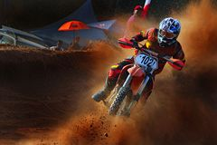 ein schroffer Motorradreiter nimmt eine scharfe Wendung im Motocrossturnier lizenzfreie stockfotografie