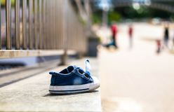 Ein Schuh auf Asphalt Traurigkeit, Konzept der vermissten Kinder Tages stockbild