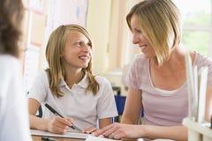 Ein Schulmädchen, das mit ihrem Lehrer in der Kategorie sitzt Stockfoto