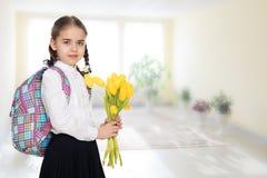 Ein Schulmädchen mit einem Blumenstrauß von Blumen und von Rucksack auf ihrem sho Lizenzfreie Stockfotos