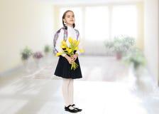 Ein Schulmädchen mit einem Blumenstrauß von Blumen und von Rucksack auf ihrem sho Lizenzfreie Stockfotografie
