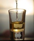 Ein Schuss eines Alkoholgetränkes, das mit dem schneienden Hintergrund getrunken wird Stockfotos