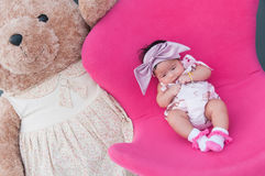 Ein Schuss eines netten Babys mit purpurrotem Stirnband und großer Teddybär, während das Schlafen und das Spielen auf dem rosa St Stockfotografie