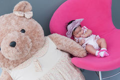 Ein Schuss eines netten Babys mit purpurrotem Stirnband und großer Teddybär, während das Schlafen und das Spielen auf dem rosa St Lizenzfreies Stockfoto