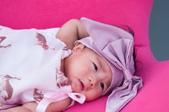 Ein Schuss eines netten Babys mit purpurrotem Stirnband, während das Schlafen und das Spielen auf dem rosa Stuhl/am Säuglingsmädc Stockfotografie
