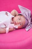 Ein Schuss eines netten Babys mit purpurrotem Stirnband, während das Schlafen und das Spielen auf dem rosa Stuhl/am Säuglingsmädc Lizenzfreies Stockfoto