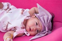 Ein Schuss eines netten Babys mit purpurrotem Stirnband, während das Schlafen und das Spielen auf dem rosa Stuhl/am Säuglingsmädc Lizenzfreies Stockbild