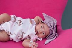 Ein Schuss eines netten Babys mit purpurrotem Stirnband, während das Schlafen und das Spielen auf dem rosa Stuhl/am Säuglingsmädc Lizenzfreie Stockfotografie