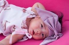 Ein Schuss eines netten Babys mit purpurrotem Stirnband, während das Schlafen und das Spielen auf dem rosa Stuhl/am Säuglingsmädc Lizenzfreie Stockbilder