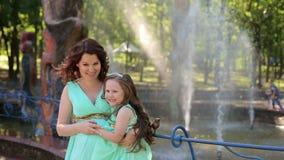 Ein schwangeres Mädchen mit ihrer Tochter nahe dem Brunnen stock video