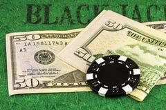 Ein schwarzer Chip liegt auf zwei 50 Dollarscheinen Lizenzfreie Stockbilder