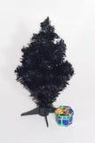 Ein schwarzer künstlicher Weihnachtsbaum mit einer Geschenk-UNO Stockfotos