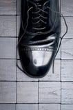 Ein schwarzer lederner Schuh mit den Spitzeen gelöst Stockfoto