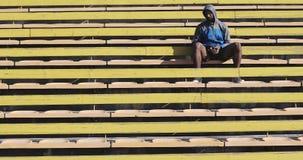 Ein schwarzer männlicher Athlet sitzt auf der gelben Treppe in einem Stadion stock video footage