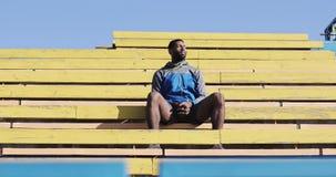 Ein schwarzer männlicher Athlet sitzt in den Ständen auf dem Stadion im Freien stock footage