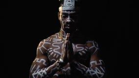 Ein schwarzer Mann in den weißen Mustern und ein Ritualhut, die auf einem schwarzen Hintergrund, Zeitlupe beten stock video