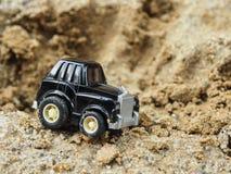 Ein schwarzer SpielzeugParkplatz im Sandkasten Lizenzfreies Stockbild