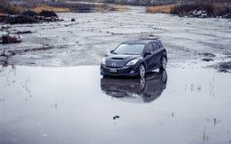 Ein schwarzes 2010 Mazdaspeed3 n ein verlassenen nass Parkplatz stockfotografie