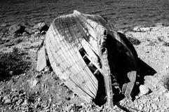 Ein Schwarzweiss-Bild eines defekten Bootes auf der Küste Lizenzfreies Stockfoto