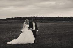 Ein Schwarzweiss-Bild eines Hochzeitspaares, das auf das fie geht Lizenzfreies Stockfoto