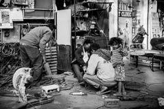 Ein Schwarzweiss-Bild mit einem indischen Jungen, der um seinen Vati spielt, während Vater arbeitet stockfotos