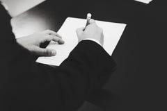 Ein Schwarzweiss-Bild von unterzeichnenden Papieren eines Mannes Lizenzfreie Stockfotografie