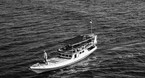 Ein Schwarzweiss-Boot mit Fischer auf die Oberseite in der Mitte von Meer lizenzfreie stockbilder