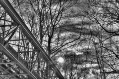 Ein Schwarzweiss-Winterfoto einer metallischen Struktur, die verschiedene Rohre auf den Betonblöcken laufen durch einen Wald stüt Stockfoto