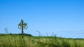 Ein schwedischer Maibaum auf einer grünen Sommerwiese stockfoto