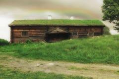 Ein schwedisches Haus 500 Jahre alt mit Gras auf seinem Dach, mitten in einer Wiese mit einem Regenbogen oben Stockbild
