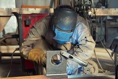 Ein Schweißer fabriziert Stahlkonstruktionen unter Verwendung des halbautomatischen weldin Lizenzfreies Stockfoto