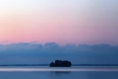 Ein See mit einer kleinen Insel, auf der die Bäume wachsen Rote vibrierende Farben Lizenzfreies Stockbild
