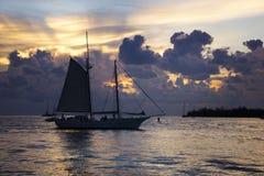 Ein Segelboot, das vor dem Sonnenuntergang und den Wolken im Ozean in Key West, Florida geht Stockbilder