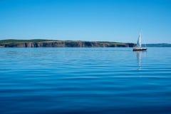 Ein Segelboot im ruhigen Wasser entlang der Küste von Neufundland stockfoto