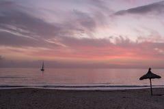 Ein Segelboot; ein mit Stroh gedeckter Strandschirm; ein schöner Sonnenuntergang, Mallorca stockfotografie