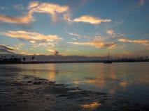 Ein Segelboot treibt während des Sonnenuntergangs auf dem Strand Stockbild