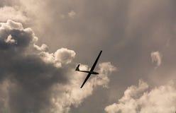 Ein Segelflugzeugfliegen im Himmel mit dem großen Bedrohen bewölkt sich Das Segelflugzeug ist eine Fläche, die keine Maschine hat stockfoto