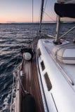 Ein Segeljachtsegeln auf dem blauen Meer während des Sonnenuntergangs Stockbild