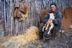 Ein sehr alter Mann in der unordentlichen Kleidung sitzt auf einem Schemel im Yard eines alten Bauernhofes und h?lt eine wei?e Zi lizenzfreies stockfoto