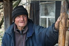 Ein sehr alter Mann in der unordentlichen Kleidung sitzt auf einem Schemel im Yard eines alten Bauernhofes und h?lt eine wei?e Zi stockbilder