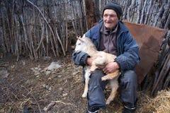 Ein sehr alter Mann in der unordentlichen Kleidung sitzt auf einem Schemel im Yard eines alten Bauernhofes und h?lt eine wei?e Zi stockfotos
