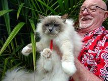Ein sehr glücklicher Mann, der seine Haustier-Katze hält stockfotos
